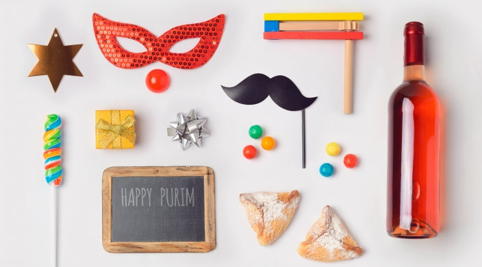 Aerial flatlay of a variety of Purim related objects and items including masks hamantaschen and a bottle of wine