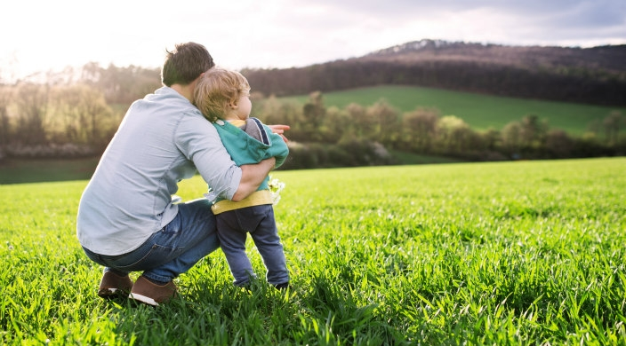 Father squatting to hold toddler in open grassy expanse with mountains in the background