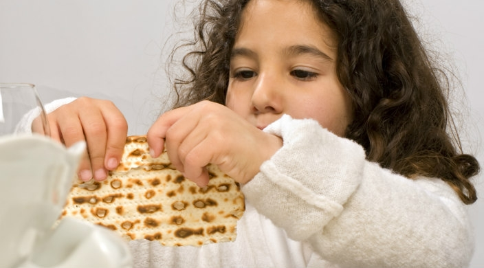 Little girl with curly brown hair holding matzah up close to her face as if to break it