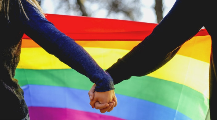 Women holding hands in front of a rainbow flag