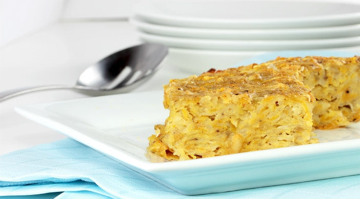 Close up of a slice of potato kugel on a white plate