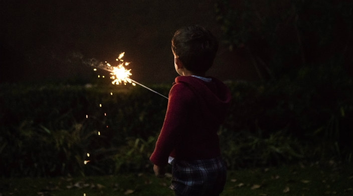 Young boy facing away from the camera while holding a sparkler in the dark
