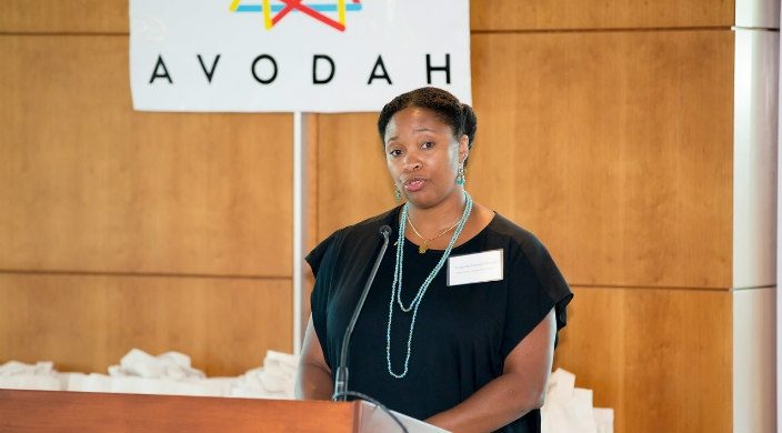 The author stands behind a wooden podium in front of an AVODAH sign