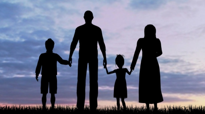 Shadowy profile of two adults and two children holding hands against a sunset
