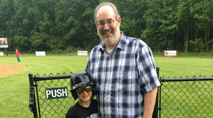 The author's son and grandson at a Little League baseball field