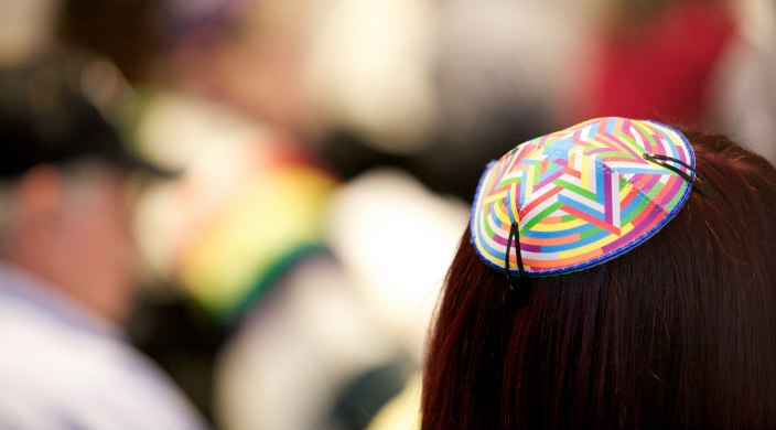 Back view of a long haired woman wearing a brightly colored kippah