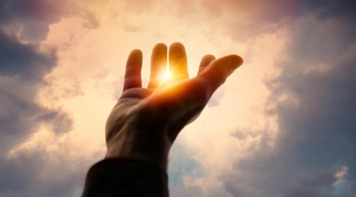 Open hand reaching skyward into the sunshine