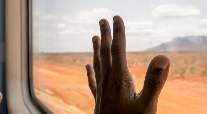 Hand of a black man against the window of a train with countryside outside