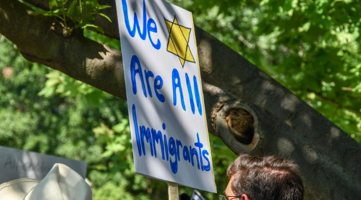 Sign reading WE ARE ALL IMMIGRANTS alongside a yellow Star of David