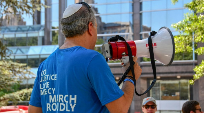 A man facing away from the camera holding a megaphone and wearing a shirt that reads DO JUSTICE LOVE MERCY WALK PROUDLY