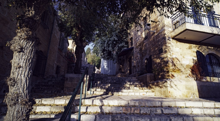 Corner of a building and a flight of stairs along a tree-lined alleyway in Jerusalem's Old City