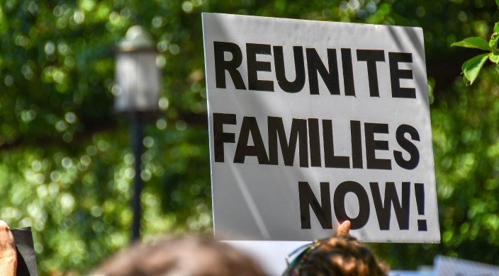 Protest sign held overhead that says: Reunite Families Now