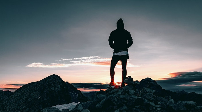 Hiker standing at the top of a mountain facing a sunset
