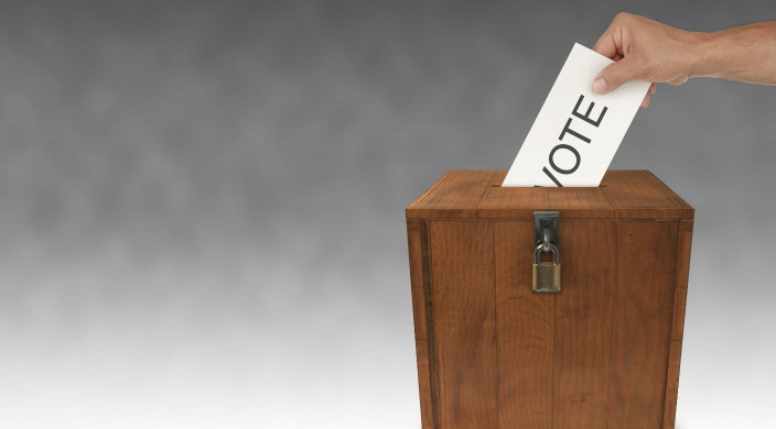"Wooden ballot box with lock into which a voter is depositing a ""ballot"" that says Vote"