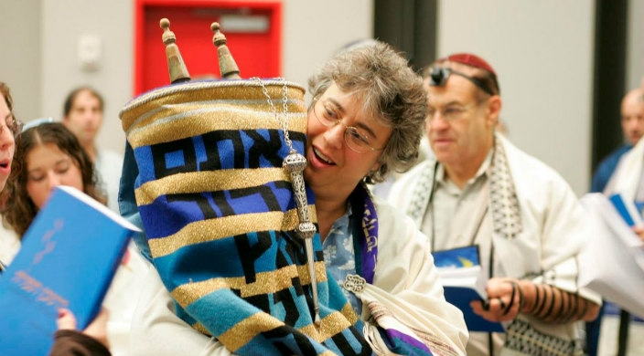 Woman holding the Torah scrolls while other celebrate behind her