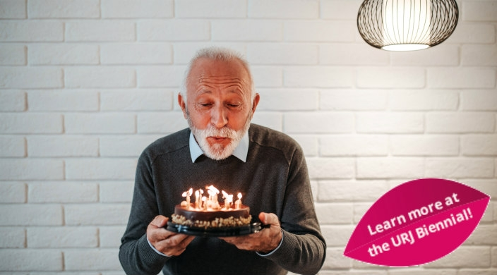 White-haired man holding a birthday cake and blowing out the candles on it