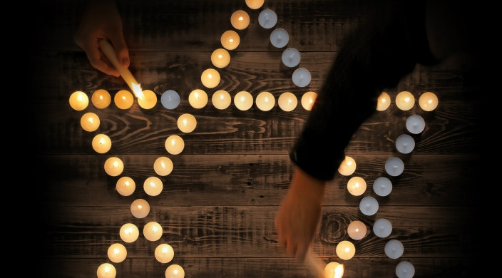 Tealights in the shape of a Star of David with hands reaching in to light some of the candles