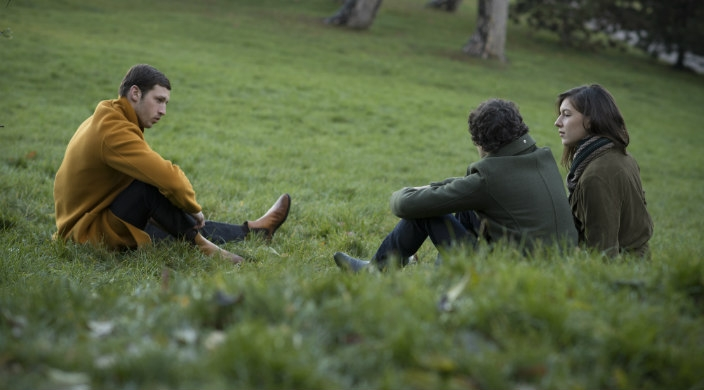 Scene from the movie: three actors (two men and one woman) sitting in a grassy field