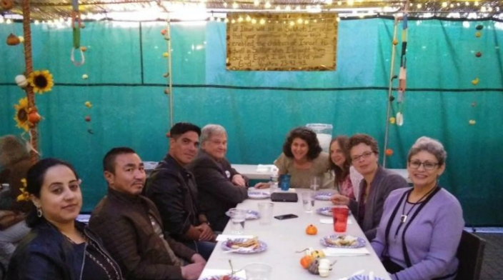 Group of people sitting at a table inside a sukkah