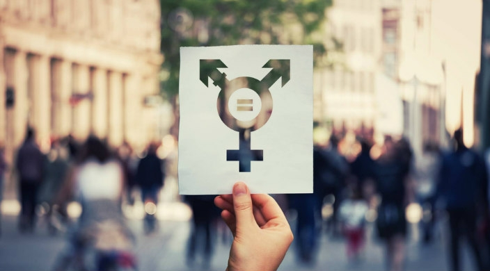 Hand holding up a sign that represents multiple genders