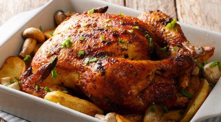 Golden brown turkey, potatoes, and mushrooms in a roasting pan
