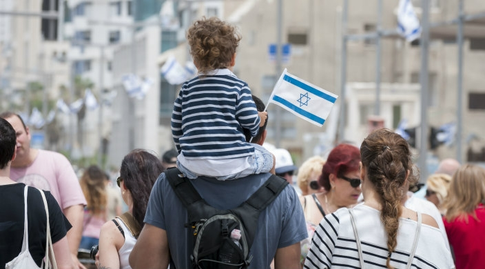 Small child holding an Israeli flag being carried on his father's shoulders