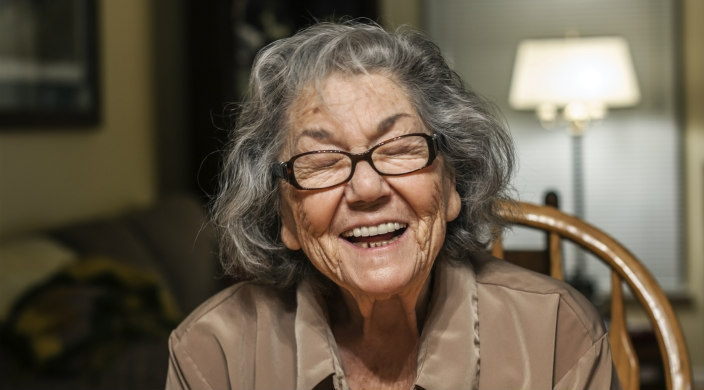 Older woman laughing toward the camera while sitting at a kitchen table