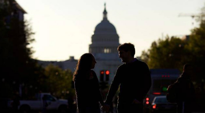 Happy couple holding hands in front of the silhouette of the US Capitol building