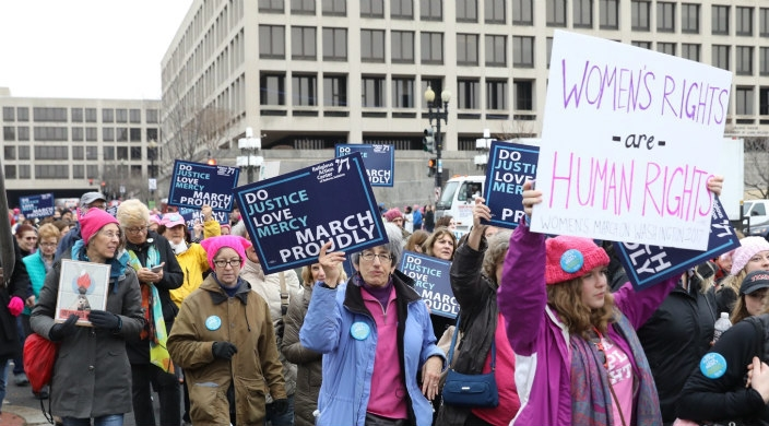 Protesters marching; one carrying a sign that says women's rights are human rights