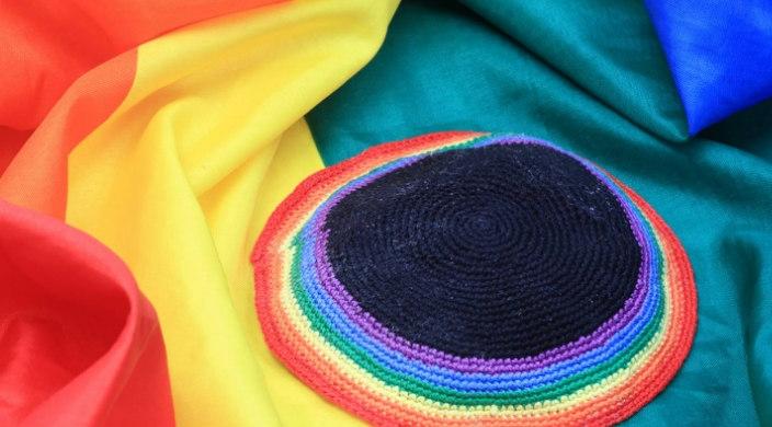 Knitted rainbow kippah resting on a rainbow flag