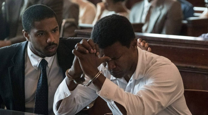 Still from the film Just Mercy showing Michael B Jordans character comforting the character played by Jamie Foxx