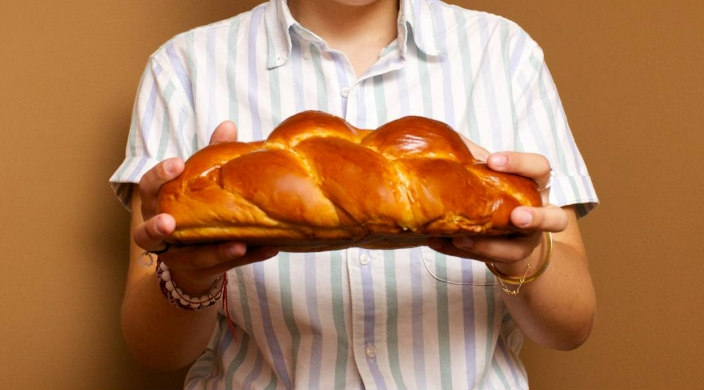 Close up of hands holding a loaf of challah against a striped shirt