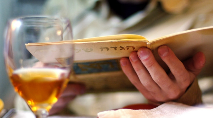 Closeup of hands holding a Haggadah with a glass of white wine in view