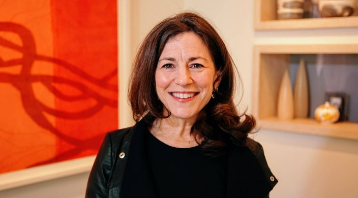 Headshot of Rabbi Carole Balin smiling at the camera against a blurred orange and red background
