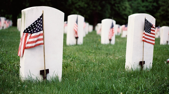 Gravestones with American flags in front of each one