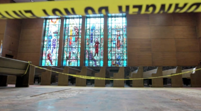 A still photo from the documentary depicting synagogue pews with yellow police tape across them and a stained window in the back
