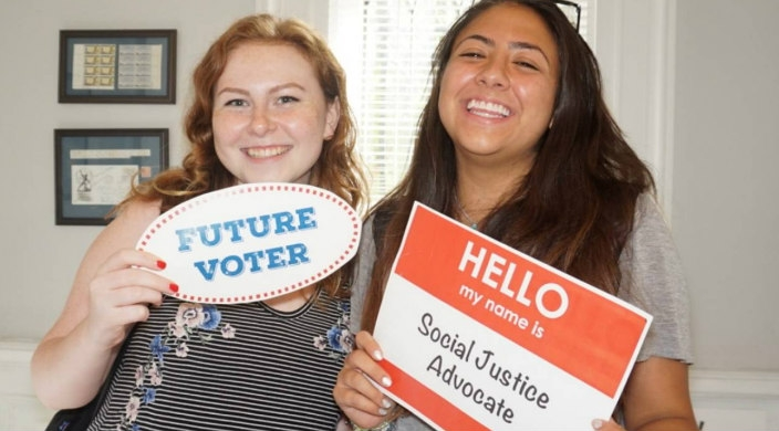 Two smiling teen girls holding signs that say FUTURE VOTER and SOCIAL JUSTICE ADVOCATE