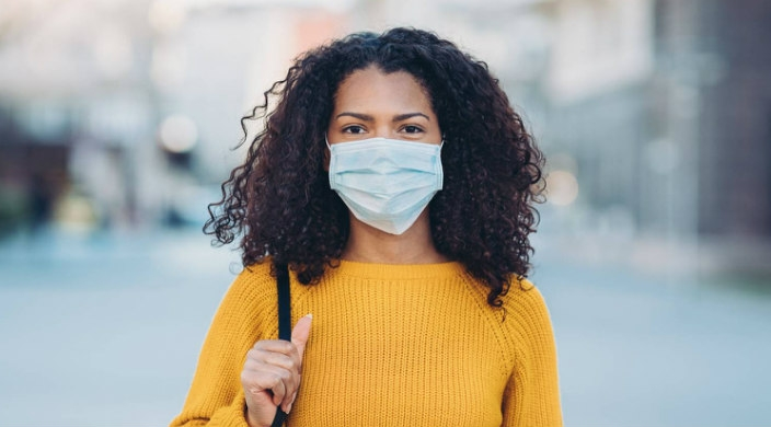 Young Black woman wearing a face mask outdoors