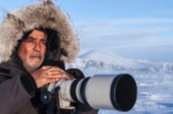 Amos Nachoum wearing a thick winter jacket and holding a large camera with an Arctic landscape visible behind him