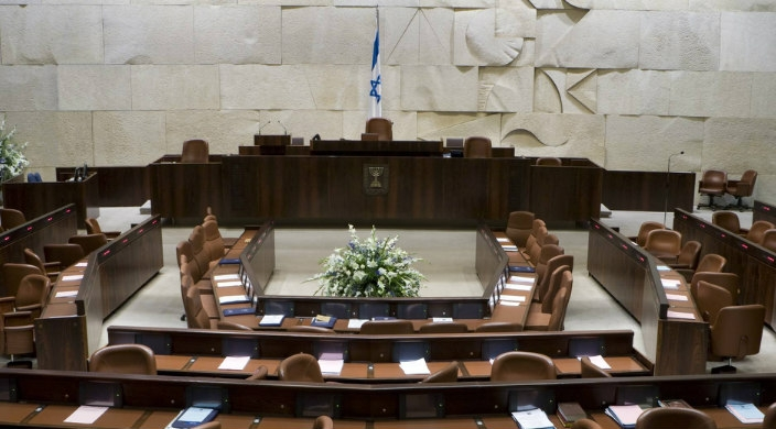 Empty chamber of the Knesset with Israeli flag at the front of the room