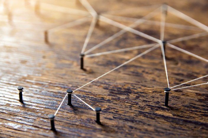 Nails in a board connected by threads to represent interconnectivity
