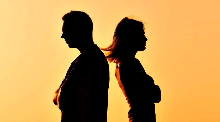 Silhouette of a man and a woman with their backs facing one another as if arguing