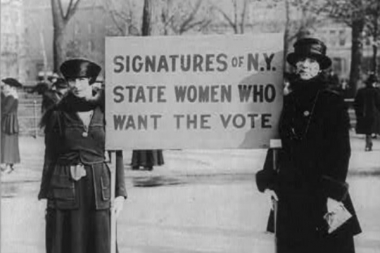 Black and white image of women suffragists holding signs in support of womens right to vote
