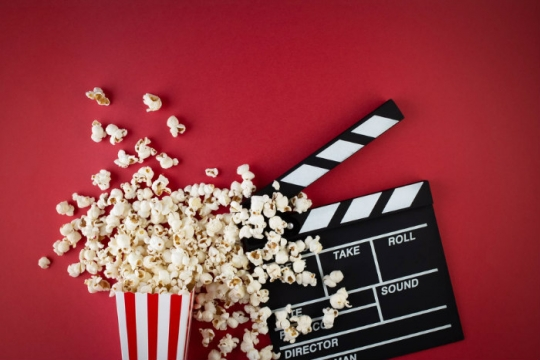 Film reel and a spilled container of popcorn against a red background