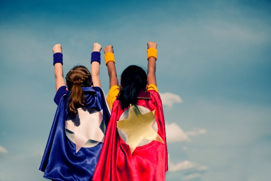 Two young girls facing forward wearing superhero capes