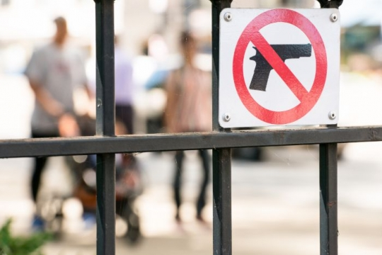Sign on a fence with a red line through a gun