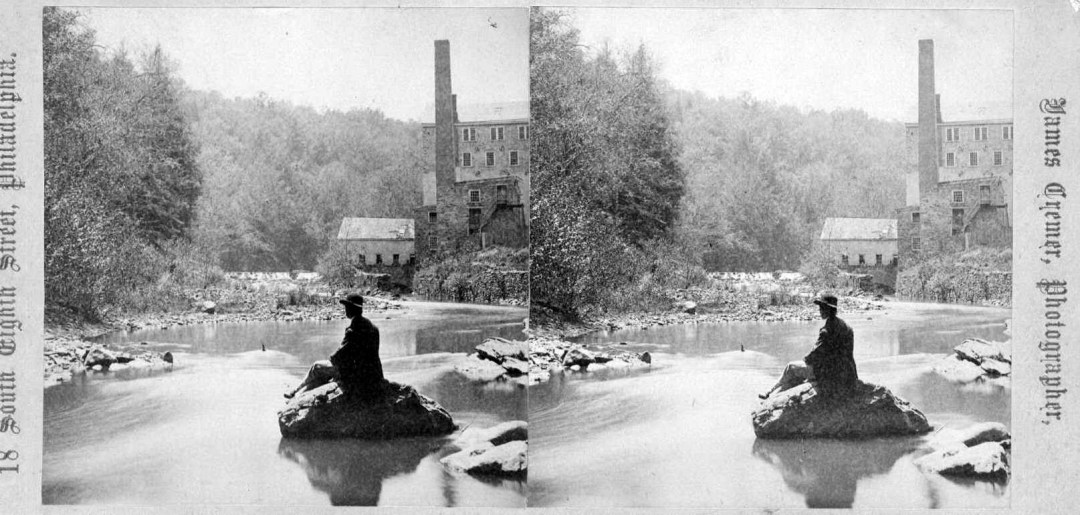 Stereoview of the Wissahickon with a stone mill on the far left. Visible are the mill buildings and two smokestacks. In the foreground is a man sitting on a rock and facing the mill. Undated, but perhaps taken circa 1865-1870.