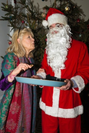 One of the party-goers receives a mince pie from Father Christmas on departure.