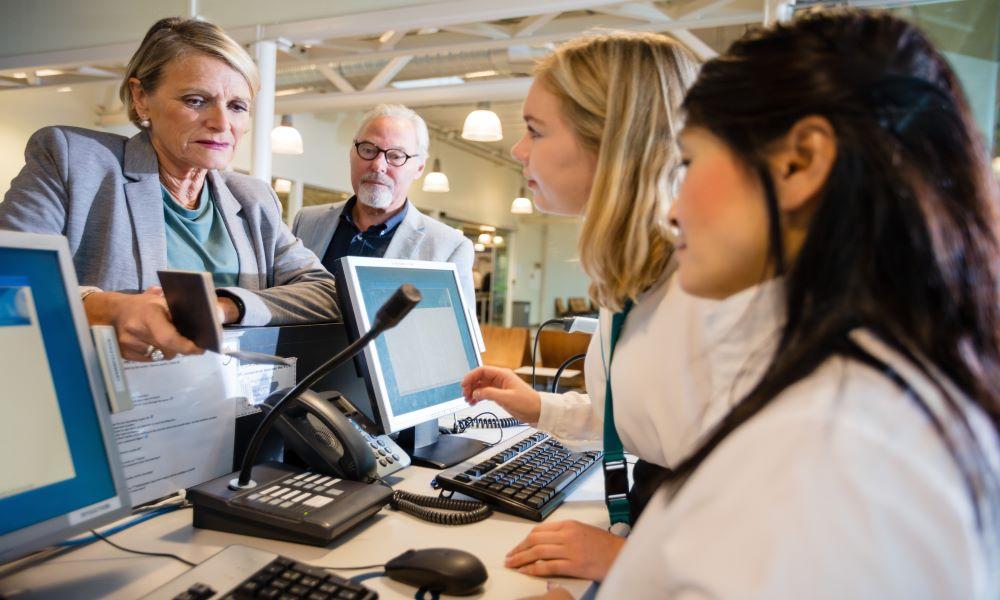 flight desk attendant helping customer find cheap first class flights