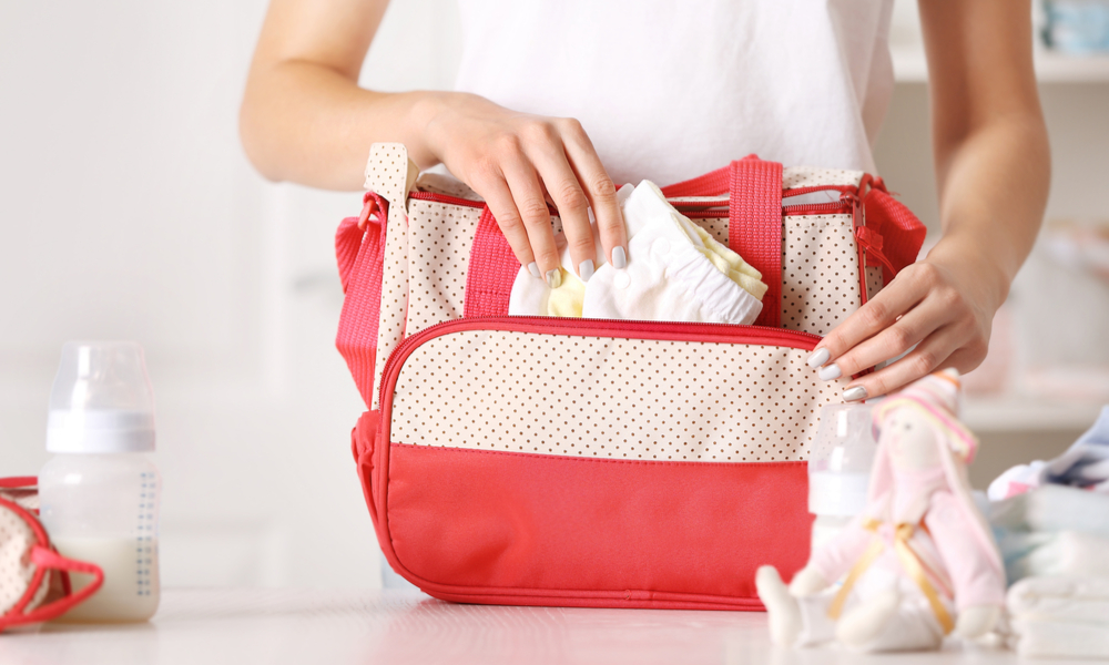How to Save When You're Traveling with Kids: Woman packing her bag with child stuff